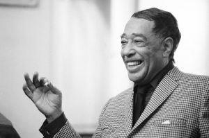 "FILE - This April 24, 1969 file photo shows musician Duke Ellington in New York. ""After Midnight,"" a joyous musical revue celebrating Duke Ellington's years at the famous Cotton Club nightclub in Harlem in the late `20s and early `30s, will begin shows downtown _ at the Brooks Atkinson Theatre on Broadway. Directed and choreographed by Warren Carlyle with musical direction by Wynton Marsalis, the show appeared off-Broadway last year at New York City Center under the name ""Cotton Club Parade."" (AP Photo/John Duricka, file)"